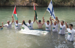 "On Aug. 15, 2010, under the auspices of EcoPeace Middle East, Israeli, Palestinian and Jordanian mayors, municipal representatives and young activists ""jumped"" into the Jordan River. The action, which took place at the Yardenit baptism site near the Sea of Galilee, called on governments to rehabilitate the polluted waterway. (Photo: Courtesy of EcoPeace Middle East)."